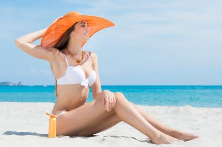 Krásná atraktivní žena v bikinách, sedící na pláži s Sun Protection Cream