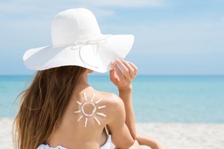 espalda: Vista posterior de una mujer joven en bikini y sol dibujado en volver con crema de protecci�n solar