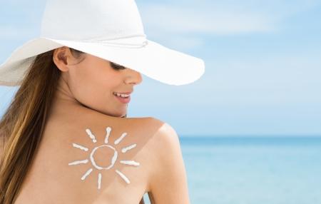 Mladá žena při pohledu na Slunce, natažený na zádech s opalovací krém