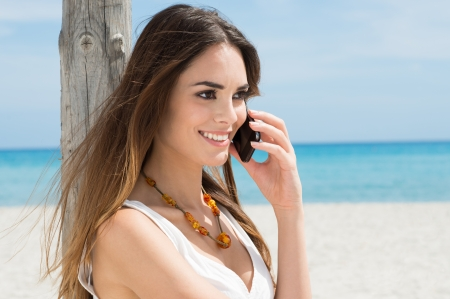 Happy Young Woman At Beach Talking On Cellphone photo