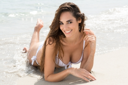 Happy Young Woman In White Bikini Lying On Wet Sand At Beach photo