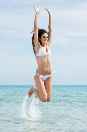 Woman Wearing White Bikini Jumping In Water At Beach photo