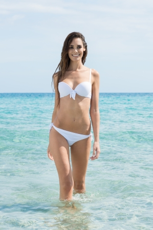Happy Young Woman In White Bikini Standing At Tropical Beach