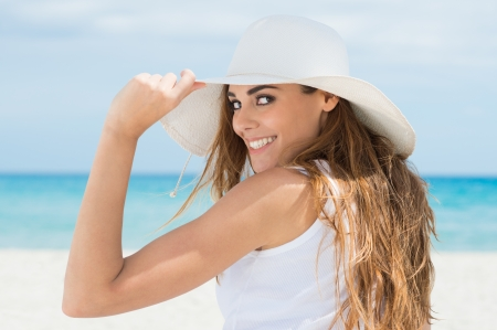 sunhat: Happy Young Woman Looking At Camera Wearing White Sunhat At Beach