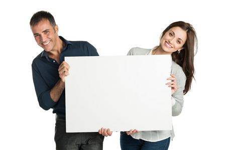 Mature Couple Looking At Camera With Sign Isolated On White Background 版權商用圖片