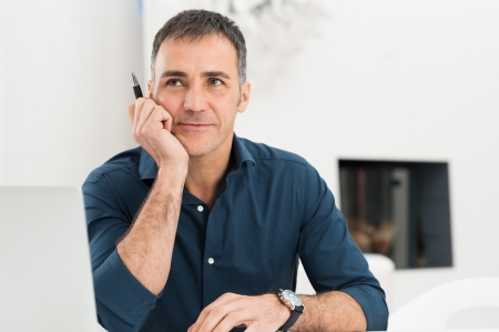 Portrait Of Mature Man Daydreaming While Holding Pen photo
