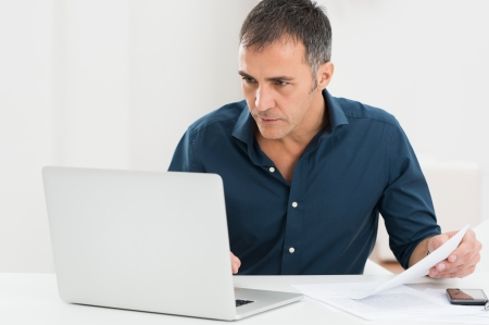 troubleshoot: Portrait Of A Mature Man Looking At Laptop Holding Document Stock Photo