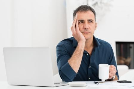 노트북과 걱정 성숙한 컵을 들고하는 사람 (남자)의 초상화