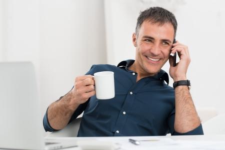 beau mec: Portrait de sourire homme d'âge mûr parlant sur le portable de fixation de tasse de café Banque d'images