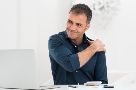 어깨 통증에서 고통 직장에서 성숙한 남자의 초상화 스톡 콘텐츠