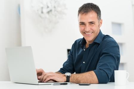 책상에 행복하여 성숙한 남자 미소 노트북의 초상화