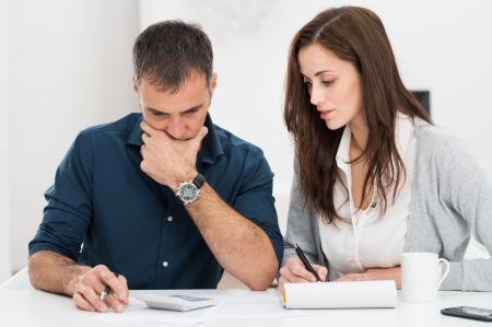 taxation: Portrait Of A Worried Couple Calculating Financial Budget