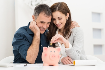 Portrait Of Happy Couple Inserting Coin In Piggybank photo