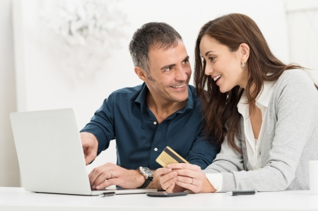 Portrait Of Happy Couple Shopping Online Using Laptop And Credit Card Stock Photo