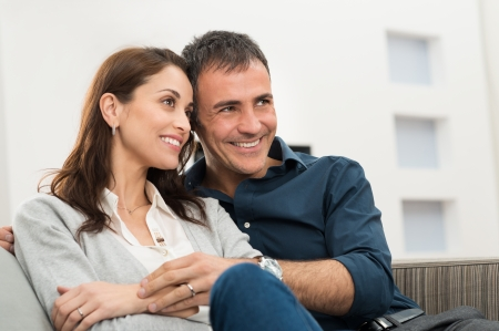 Portrait Of A Happy Couple Embracing Sitting On Couch photo