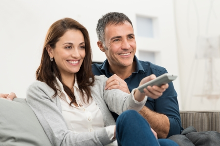 Pares sonrientes felices viendo la televisión en casa