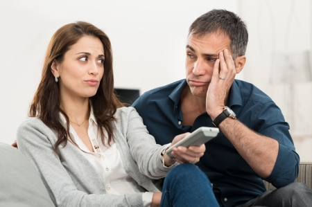 Frustrated Couple Looking At Each Other While Watching Television Sitting On Couch Stock Photo