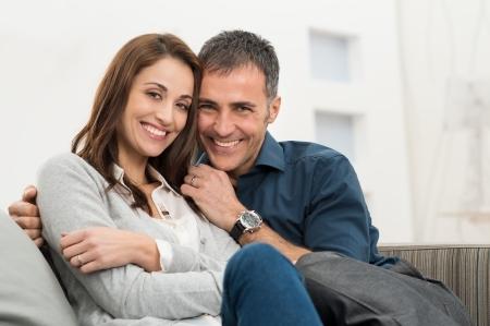 uomini maturi: Coppia felice che abbraccia seduto sul divano guardando verso l'obiettivo