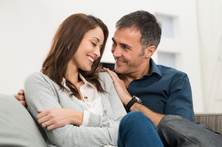 latin people: Portrait Of Happy Loving Couple Sitting On Couch At Home