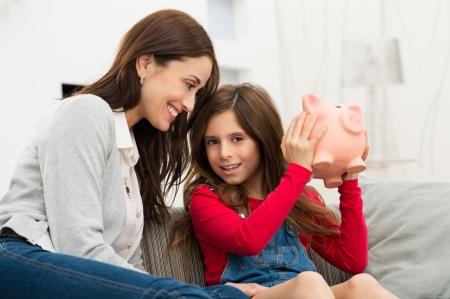 Piggybank を保持しているソファに座って彼女の娘を見て笑顔の母