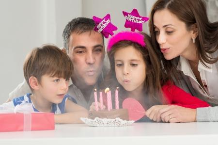 празднование: Портрет Счастливая семья дует свечи на день рождения торт вместе Фото со стока