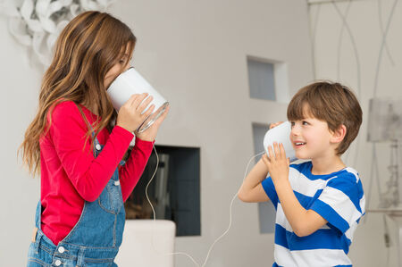 tin can: Cute Little Boy Listening To His Sister Speaking Through Tin Can Phone Stock Photo
