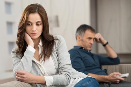 personas discutiendo: Pareja triste que se sienta en el sofá después que disputa Foto de archivo