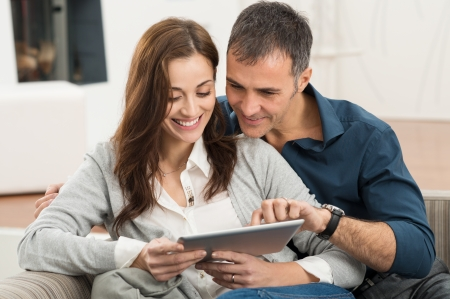 Portrait Of Happy Couple Sitting On Couch At Home Using Digital Tablet Stock Photo