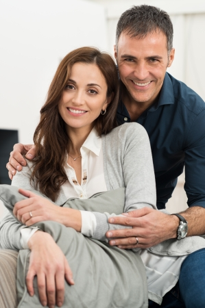 Portrait Of Happy Loving Couple Sitting On Couch Looking At Camera