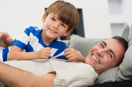 padre e hijo: Retrato del padre y del hijo Juguetón Disfrutar En El Sofá Foto de archivo