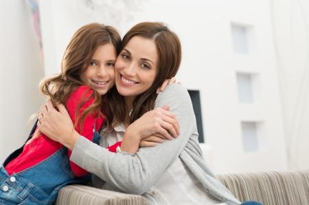 Portret van gelukkige moeder en dochter omhelzen van de camera kijken Stockfoto