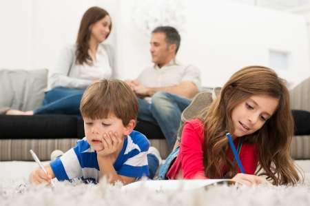 兄と妹が両親の前で、カーペットの図面の上に横たわる