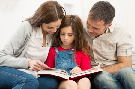 parenthood: Mother And Father Helping Their Daughter While Reading Book