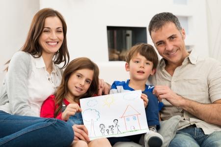 Lachende ouders met kinderen Zittend op de bank weer samen Tekening van een nieuw huis Stockfoto