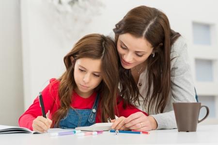 deberes: Feliz Joven Madre ayudando a su hija, mientras estudiaba en el hogar
