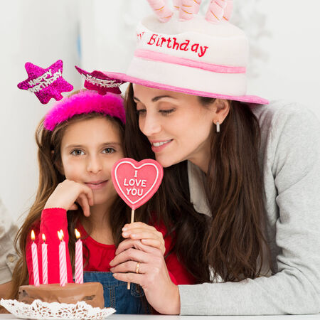 Closeup Of A Mother With Her Daughter In Front Of Birthday Cake photo
