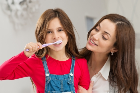 Happy Young Mother Looking At Her Daughter Brushing Teeth photo