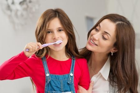 mujeres latinas: Madre feliz joven que mira a su hija cepillarse los dientes