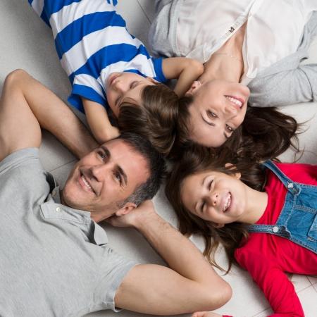 高視角幸福的家庭有兩個孩子躺在地上