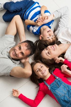 家庭: 幸福的家庭有兩個孩子躺在地板上