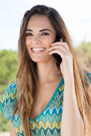 Portrait Of A Smiling Girl Talking On Cellphone photo