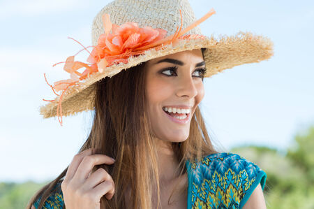 Portrait Of Cheerful Young Woman With Floral Sunhat photo