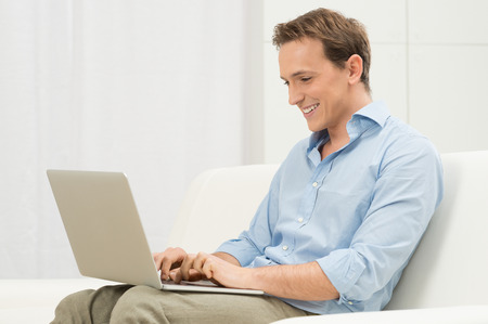 Happy Man Relaxing On Sofa Using Computer photo