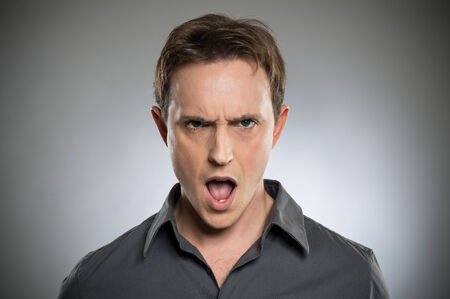 shocked face: Portrait Of Angry Young Man Shouting Over Grey Background