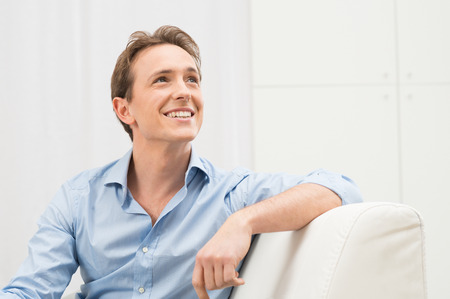 contemplated: Happy Young Man Sitting On Sofa Looking Up