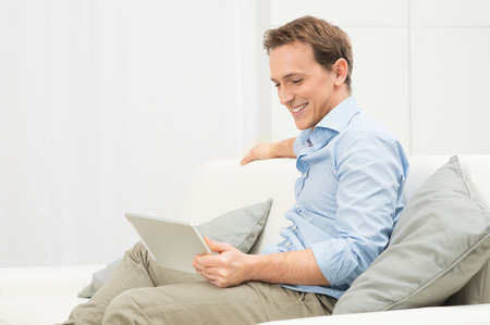 Portrait Of Happy Man On Sofa Looking At Laptop photo