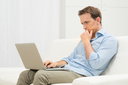 beau mec: Jeune homme s�rieux travail avec un ordinateur portable sur le sofa blanc Banque d'images