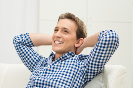 Happy Young Man With Hand Behind Head Contemplating photo