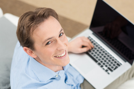 Happy Young Man Working On Laptop And Looking At Camera photo