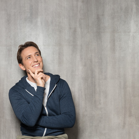 Young Happy Man In Blue Sweatshirt Thinking photo